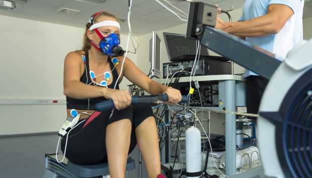 A person connected to testing machinery wears a mask and has electodes stuck to their chest and stomach. She performs rows on a rowing machine. A professional stands her at a computer where the testing machinery is connected.