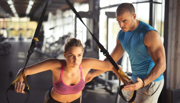 A determined woman exhales as she trains in a gym using a suspension training system while her personal trainer supports her.