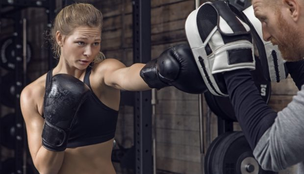 A fit boxer aims at her coach's punching pad and makes a strike as the trainer steadily holds up two pads with each hand.