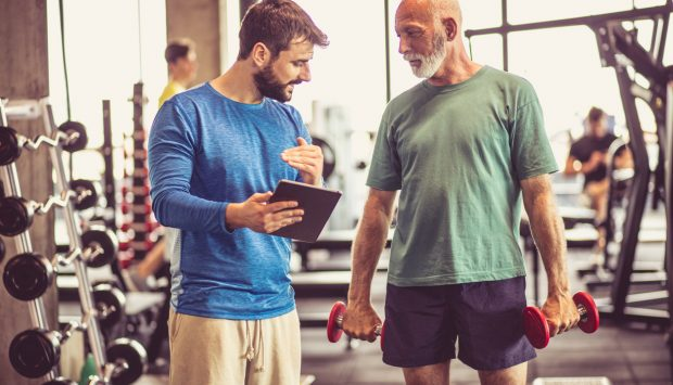 A man at a gym holding two dumbbells listens to his personal trainer as they coach him.