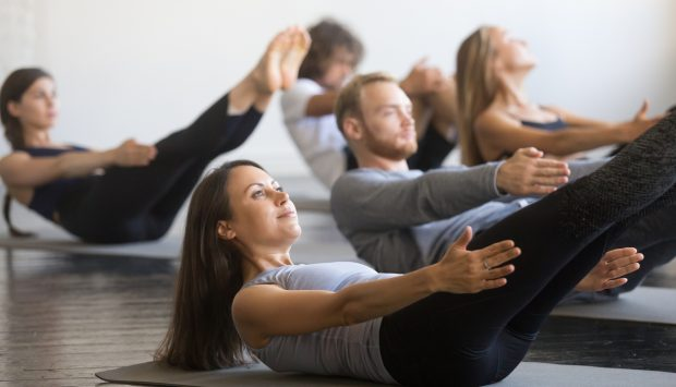 A group of fit individuals lay on yoga mats in a studio and perform a V-shaped pose.