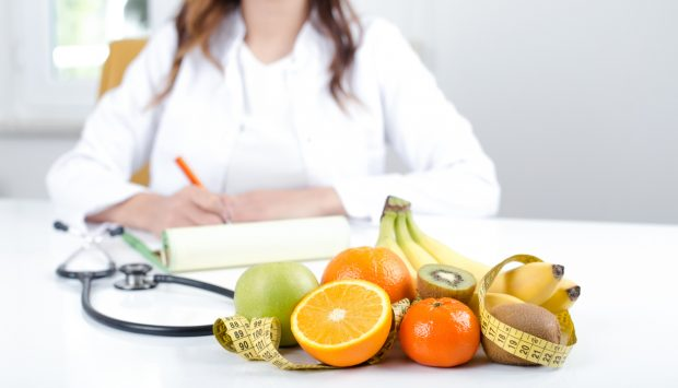 Measuring tape is woven in fruit as a doctor sits at a table in front of a clipboard and a stethoscope.