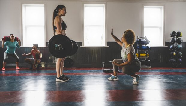 In a gym, a professional athlete performs a deadlift while standing across from her coach. The coach is squated down with one hand in the air to signal the athlete. In the background, another coach and athlete pair work together.