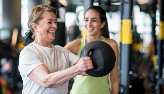 A smiling woman accompanied by her personal trainer completes a workout by lifting a weighted excersise ball in a gym.