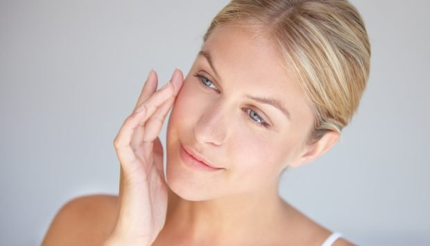 Woman inspects wrinkle-free face