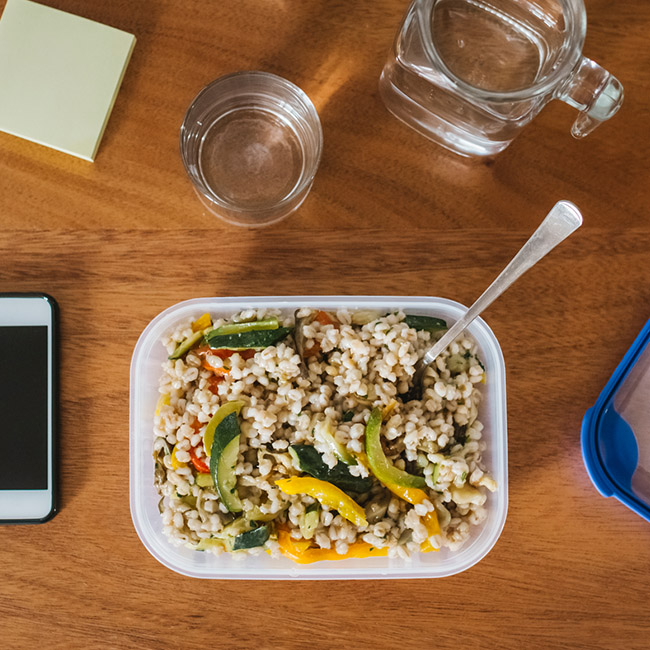 A healthy lunch sits on a desk surrounded by a smartphone, two glasses, a sticky notepad and the cover of the food container.