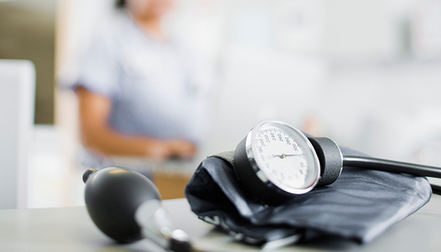A sphygmomanometer sits on a clinic desk after being used during a cardiovascular health assessment