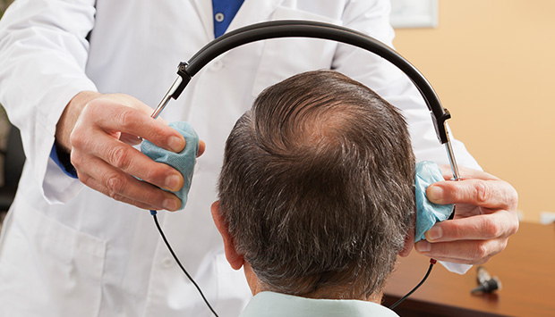 A technician places headphones on a patient as part of an audiology test.