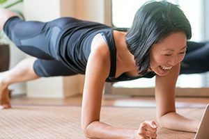 A cheerful woman performs a plank in her home. One leg is off the ground as she smiles at her laptop screen.