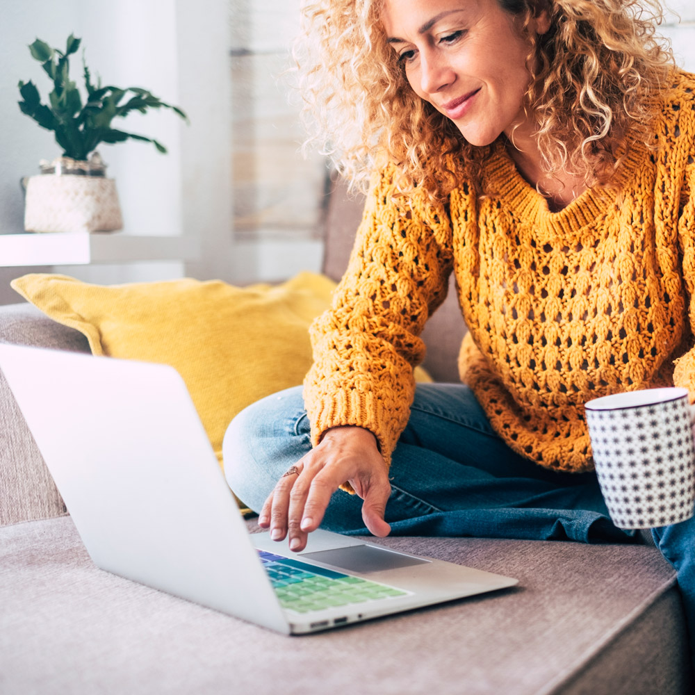 Woman in cheery yellow, knit sweater browses on a computer while sitting on her couch.