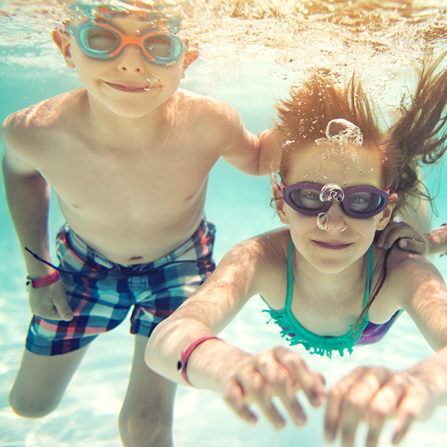 Two healthy children swimming in a pool.