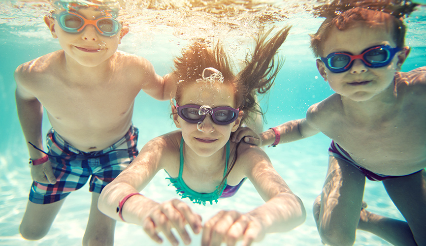 Healthy young children swim in pool