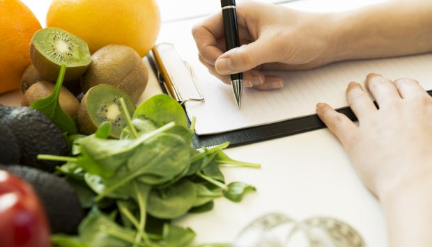 Person holds a pen to a clipboard surrounded by a spread of colourful fruits and vegetables.
