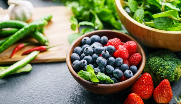 Blueberries and rasberries are in a bowl with garnishing. It is surrounded by strawberries, broccoli, peppers and leafy greens. Garlic sits in the background.