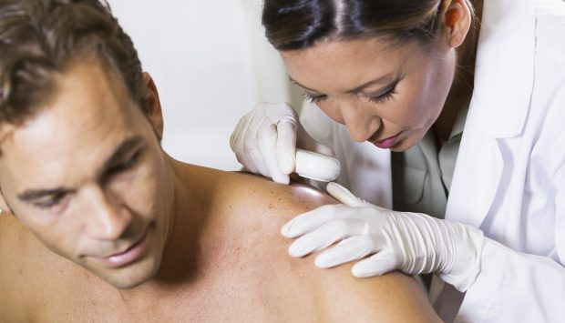 Dermatologist inspects marks on patient's skin
