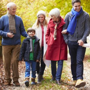 Three generations of family walk together outdoors