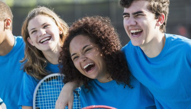 A group of cheerful youth holding tennis rackets smile. One youth places their arm around another.