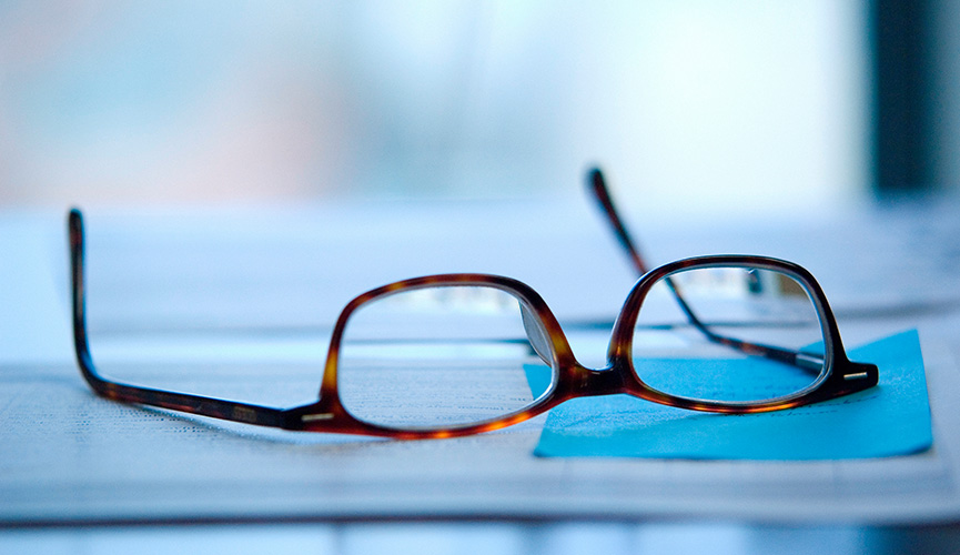A pair of glasses sit on a table.