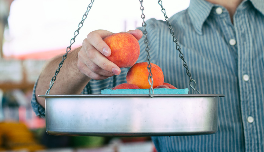 Man weighs fresh peaches on a scale in a grocery store