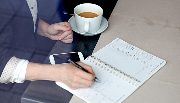 A woman pencils in her annual health assessment into her schedule agenda