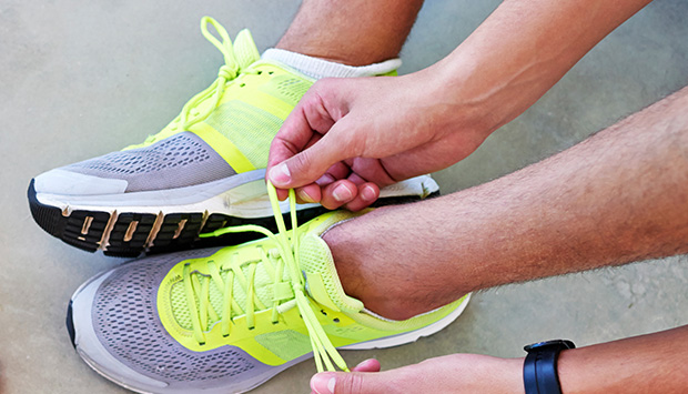 A man ties his shoes in preparation for a run