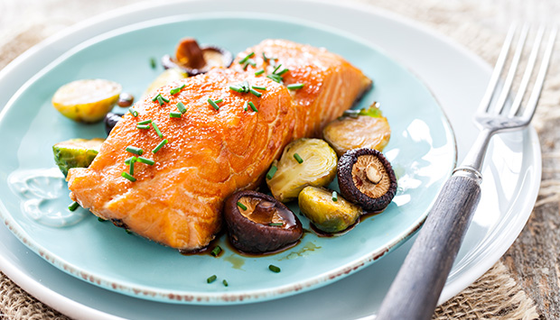 A warm piece of salmon garnished with freshly-chopped chives is presented on a light blue plate with a side of roasted mushrooms and Brussel sprouts.