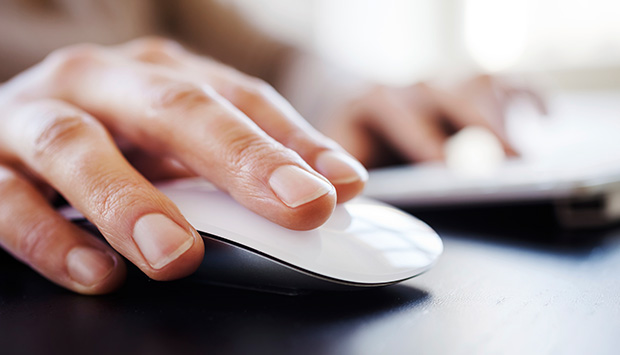 Person has one hand on a computer mouse while their other hand is on a device in the background.
