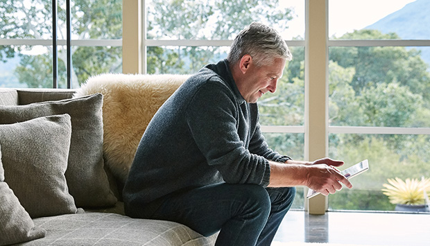Man sits on his living room couch looking at a tablet with a smile. The room has big windows overlooking a forest.