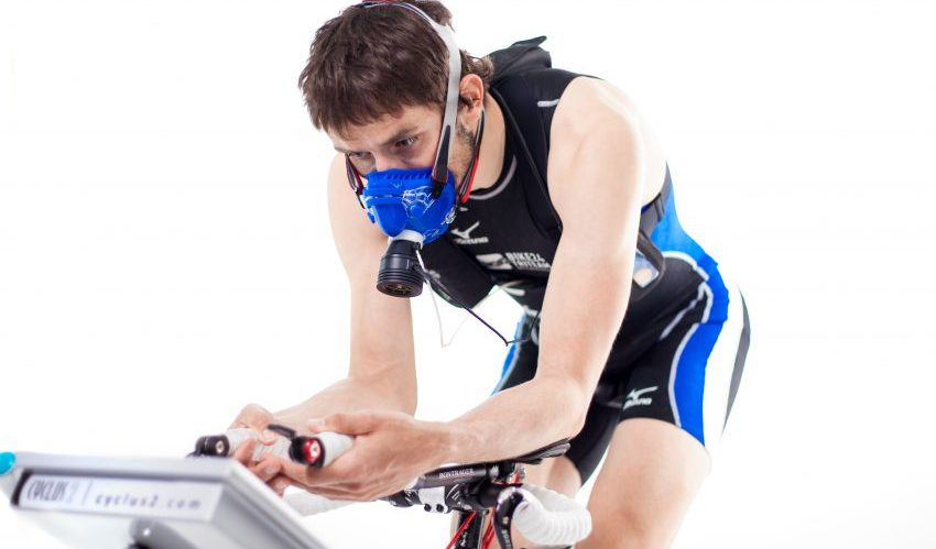 Professional cyclist wears mask and rides on stationary bike.