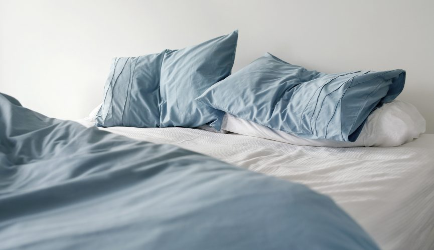 Empty bed with blue sheets