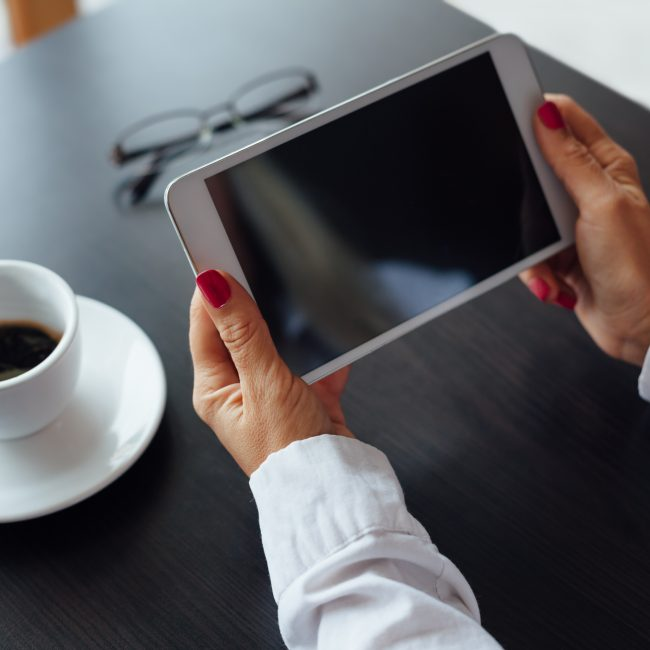 Closeup of women holding new white tablet on black table