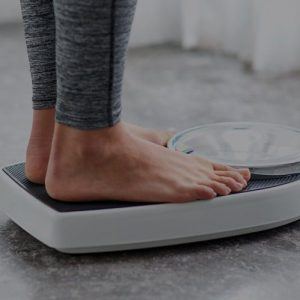 Person standing on a scale weighing themselves