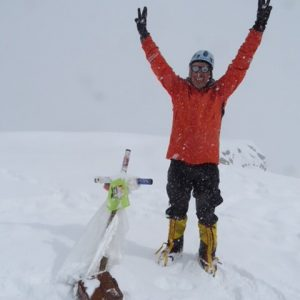 Proud mountain climber with arms in the air standing at a summit.
