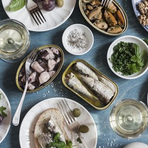 Snacks table - canned sardines, mussels, octopus, grape, olives, tomato