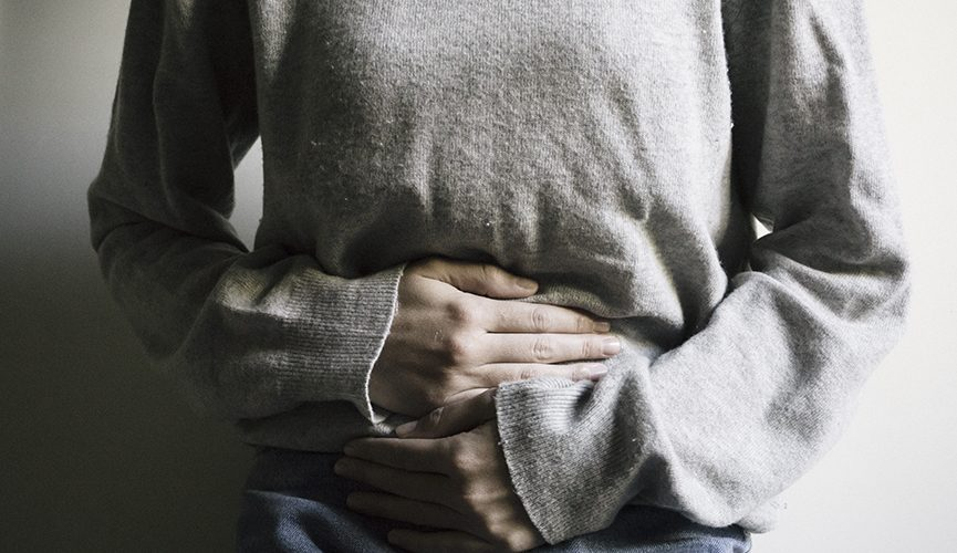 Person holding their stomach in pain