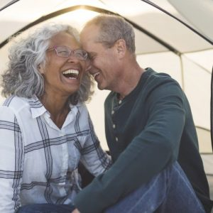 Retired couple laughing in a tent