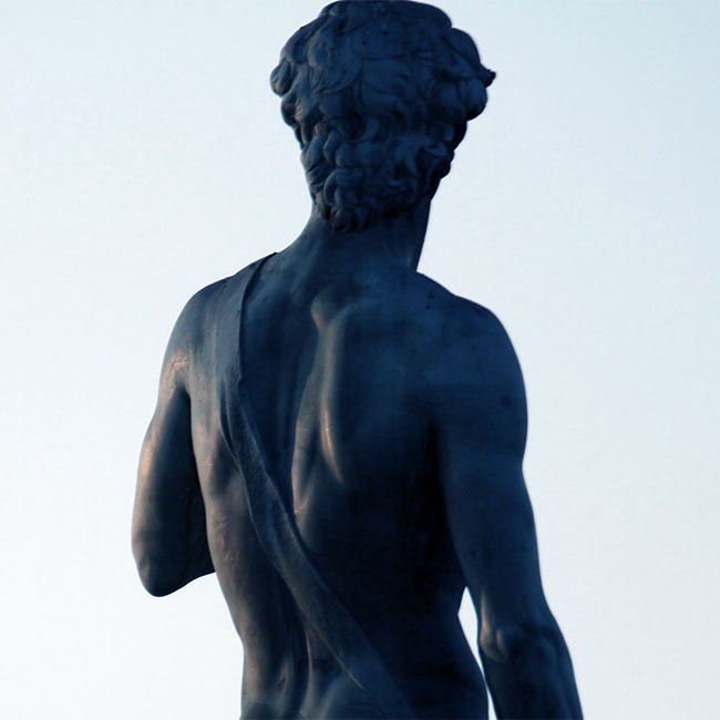 Stone statue of man with his back facing the camera