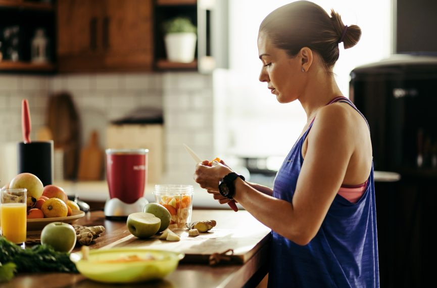 A spread of fruit sit on a counter as a fit person cuts fruit into a blender.