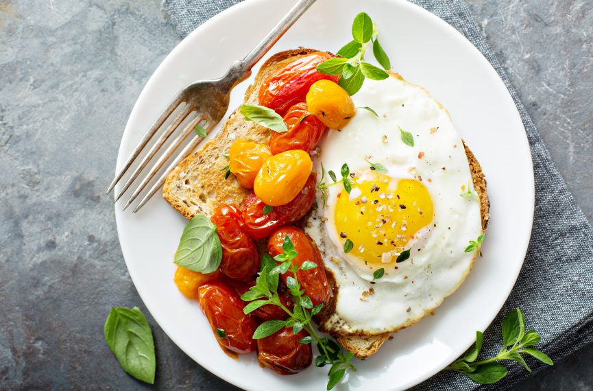 Healthy breakfast consisting of toast, eggs, grape tomatoes and garnishing.