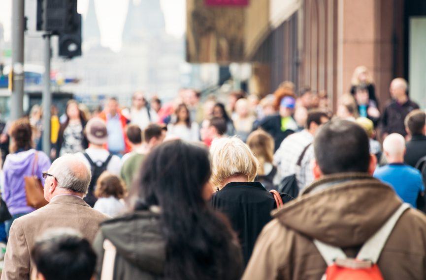People walk through the crowded core of a major city