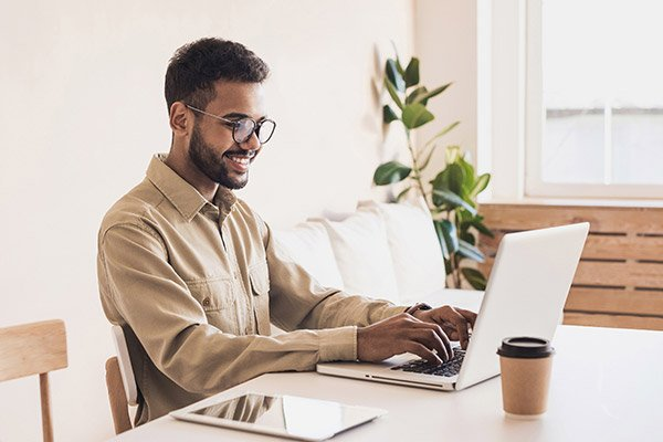 A smiling man wearing glasses working from home on his laptop.