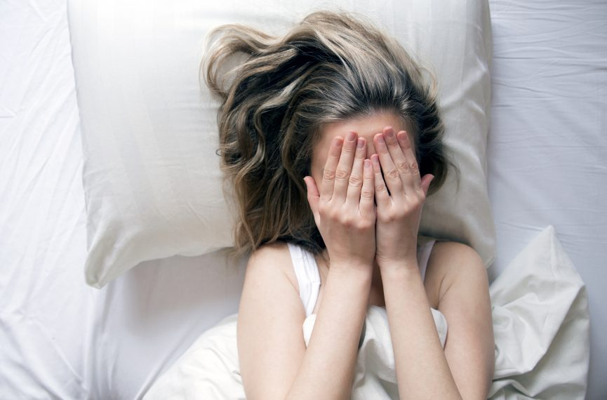 Woman lying in bed covering her face