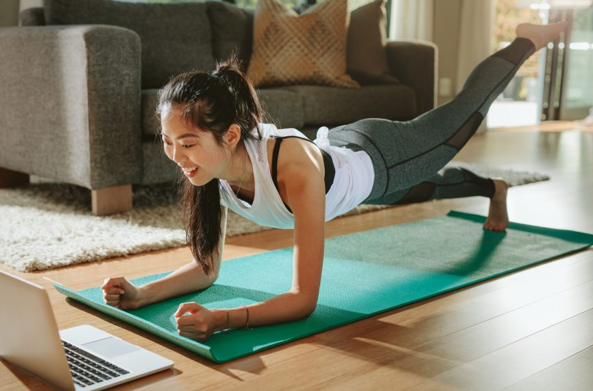 Smiling woman exercising at home and watching training videos on laptop.