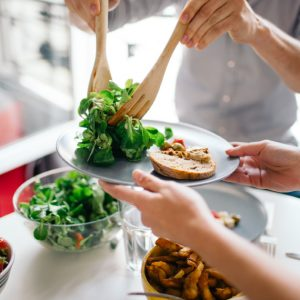 a person serving a portion of salad